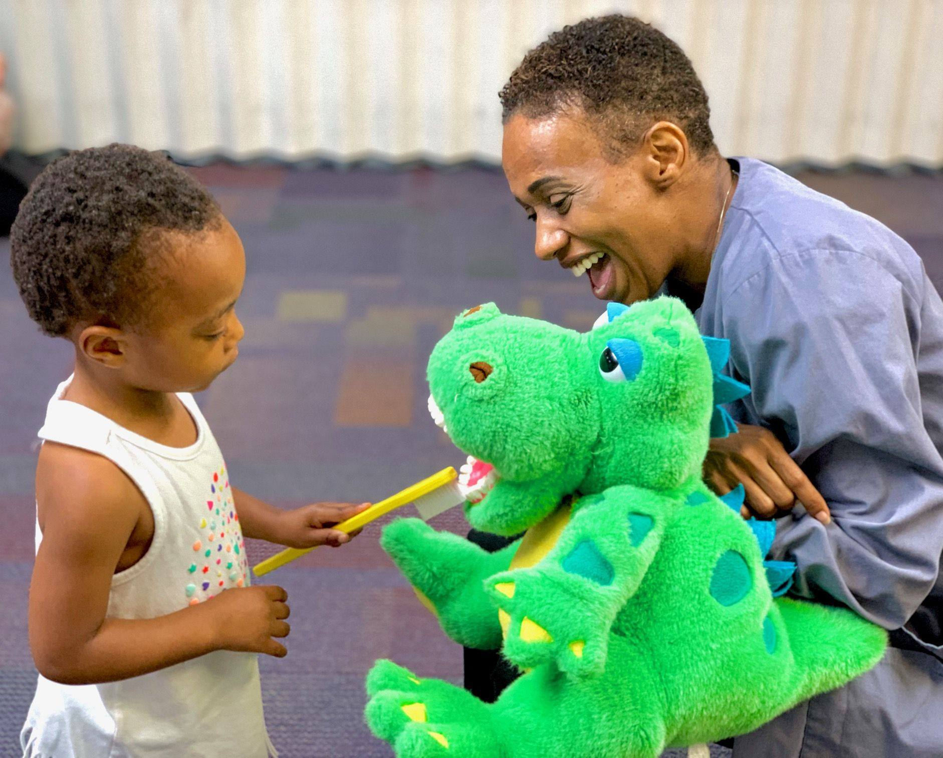 little kid brushing puppets teeth with staff member